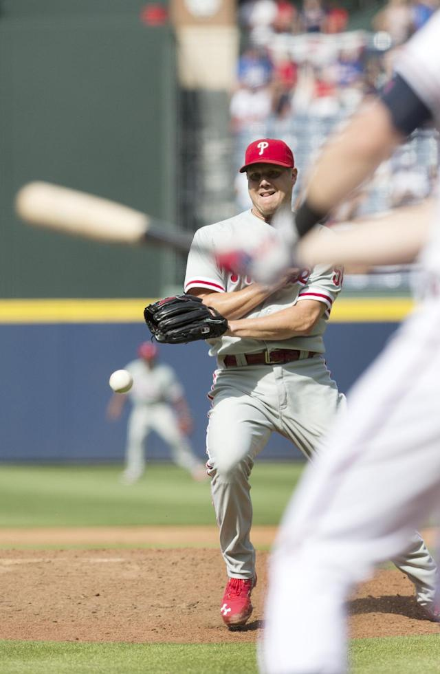 Philadelphia Phillies relief pitcher Jonathan Papelbon tries to field a ball hit up the middle by Atlanta Braves' Chris Johnson in the ninth inning of a baseball game Monday, Sept. 1, 2014, in Atlanta. Papelbon combined with starting pitcher Cole Hamels, and relief pitchers Ken Giles and Jake Diekman for a no hitter. The ball was fielded and Johnson throw out at first for the final out of the game. (AP Photo/John Bazemore)