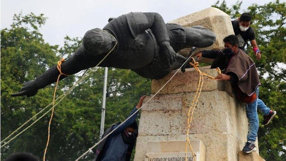 """Protesters knock down the statue of the founder of the city, Spanish conqueror Sebastian de Belalcazar, during the protests against the tax reform called by the workers"""" centrals in Cali, Colombia, 28 April 2021"""