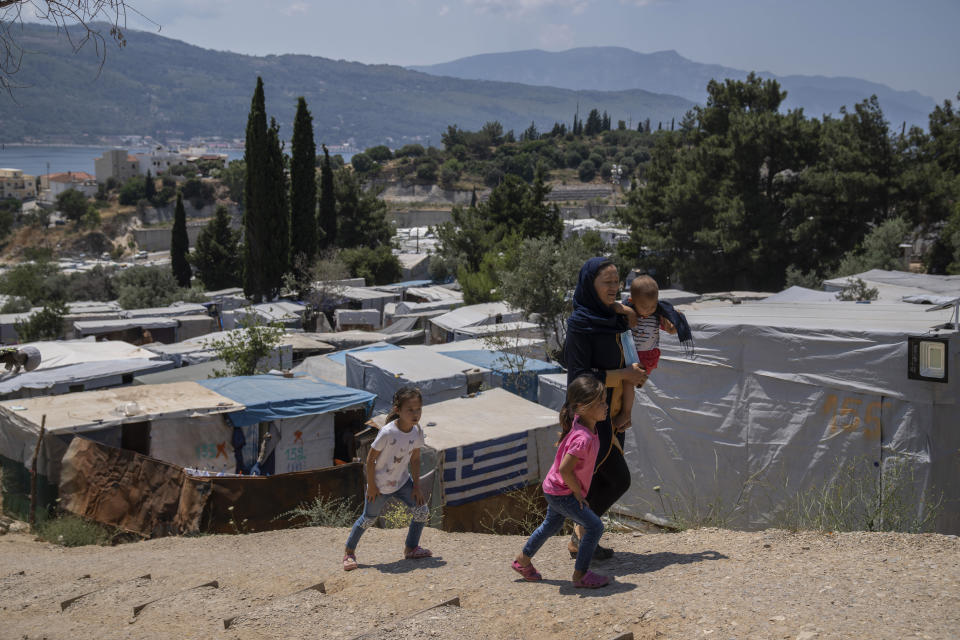 An Afghan woman with her three children walk outside the perimeter of the refugee camp at the port of Vathy on the eastern Aegean island of Samos, Greece, on Friday, June 11, 2021. An inflatable dinghy carrying nearly three dozen people reached the Greek island of Samos from the nearby Turkish coast. Within 24 hours, refugee rights groups say, the same group was seen drifting in a life raft back to Turkey. But of the 32 people determined to have initially made it to Samos, only 28 were in the raft the Turkish coast guard retrieved at sea. (AP Photo/Petros Giannakouris)