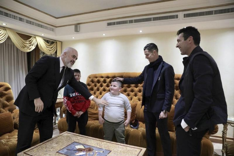 Albanian Prime Minister Edi Rama, left, Juventus' players Cristiano Ronaldo, second right, and Gianluigi Buffon, right, meet with Aurel Lala and Alesio Cakoni, in Rome on Friday, Dec. 6, 2019. The two Albanian children were injured when they escaped their collapsing flat jolted from the Nov. 26 6.4-magnitude earthquake, that killed 51 persons and injured more than 3,000 others. They lost each two family members but their dream came true when Rama took them to Rome, Italy to meet with their sport idols Ronaldo and Buffon. (Albanian Prime Minister Office via AP)