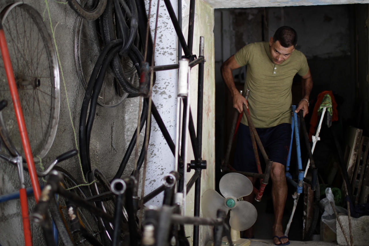 In this June 1, 2012 photo, Felix Guirola carry bicycle frames at his home in Havana, Cuba. Guirola has been riding tall since 1983, when seeing a tandem bike inspired him to build up instead of out. He said his first tall bike measured 5.3 feet (1.6 meters), and they got progressively taller until five years later he was riding 18 feet (5.5 meters) in the air at Ciego de Avila carnivals. (AP Photo/Franklin Reyes)