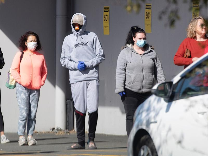Peoplewearing face masks, stand in aqueueto enter a shopin Christchurch, New Zealand, on March 25, 2020.