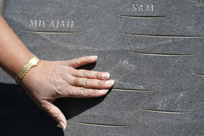 """Cauline Yates, descendant of one of Thomas Jefferson's slave mistresses, points out names inscribed in the walls of the Memorial to Enslaved Laborers at the University of Virginia in Charlottesville, Va., Thursday, May 6, 2021. """"It's time for them to stand up and honor our ancestors,"""" said the Charlottesville resident, who recently co-founded a group advocating for UVA's slave descendants. (AP Photo/Steve Helber)"""
