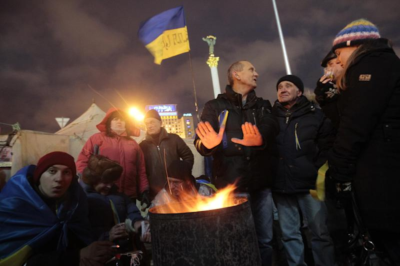 Protesters warm themselves around a fire in Independent Square in Kiev, Ukraine, Saturday, Dec. 7, 2013. As thousands of anti-government protesters kept their vigil in Ukraine's capital Saturday, officials sought to reduce their anger with assurances that Russian and Ukrainian presidents didn't discuss Ukraine joining a Russian-led customs union at a meeting this week. (AP Photo/Sergei Chuzavkov)