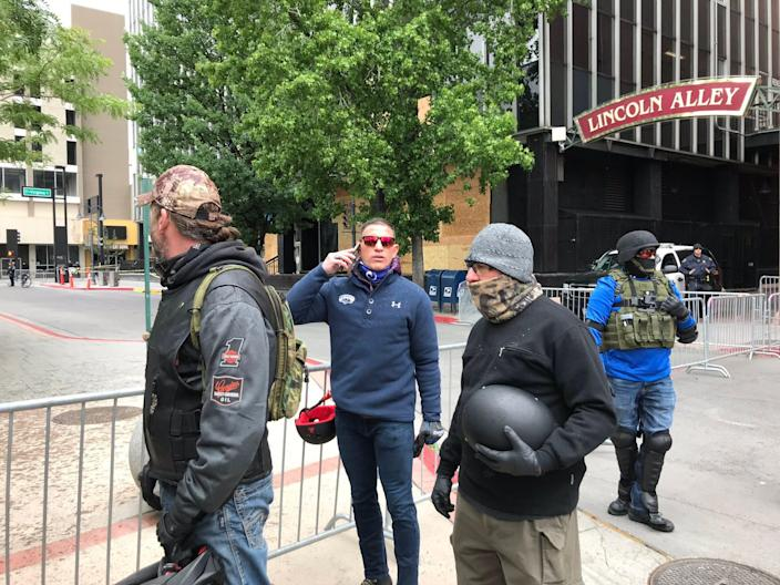 """A small group of men in tactical gear arrive to a Reno Black Lives Matter peace vigil with Joey Gilbert, center on phone, a local lawyer who sued the state over the use of chloroquine for the coronavirus. They said they don't believe the police did enough to protect the city and were at the peace vigil """"in support"""" June 7, 2020."""