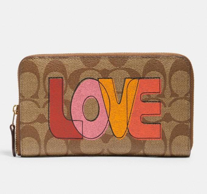 Medium Id Zip Wallet In Signature Canvas With Love Print. Image via Coach Outlet.
