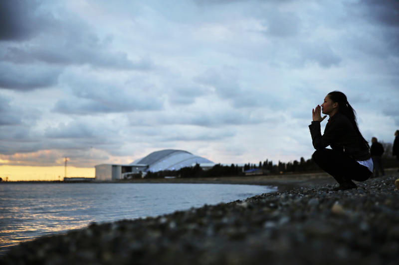 Elina Suyundikova, a dancer in the 2014 Winter Olympics opening ceremony, watches the sunset along the Black Sea while returning from a rehearsal on the eve of the performance and the games' official opening at Fisht Olympic Stadium, seen in the background, Thursday, Feb. 6, 2014, in Sochi, Russia. (AP Photo/David Goldman)