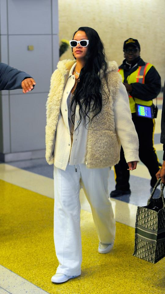 "<p>While leaving JFK in 2019, <a class=""sugar-inline-link ga-track"" title=""Latest photos and news for Rihanna"" href=""https://www.popsugar.com/Rihanna"" target=""_blank"" data-ga-category=""Related"" data-ga-label=""https://www.popsugar.com/Rihanna"" data-ga-action=""&lt;-related-&gt; Links"">Rihanna</a> was seen wearing a white set with a fuzzy vest and white sneakers.</p>"