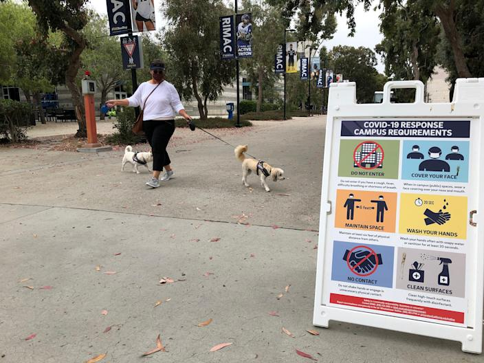 Marina Bruce, an assistant director of admissions at the University of California-San Diego, takes her dogs for a walk amid signs outlining COVID-19 precautions.
