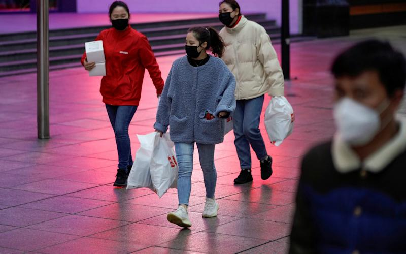 People wear masks at a main shopping area, in downtown Shanghai - ALY SONG / REUTERS