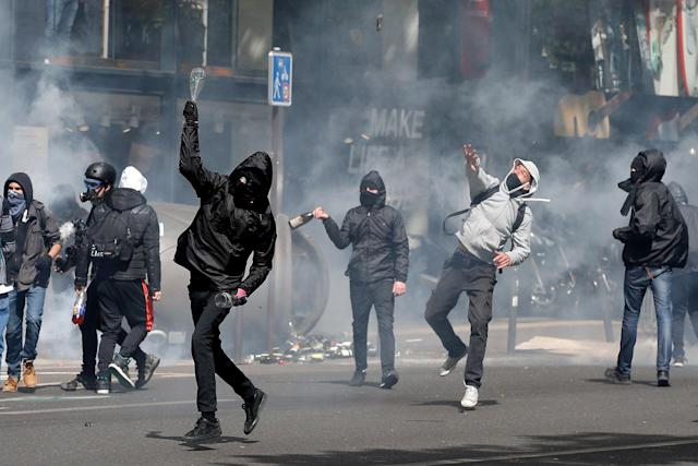 <p>Hooded youths throw bottles during clashes at a demonstration to protest the results of the first round of the presidential election in Paris, France, April 27, 2017. (Gonzalo Fuentes/Reuters) </p>