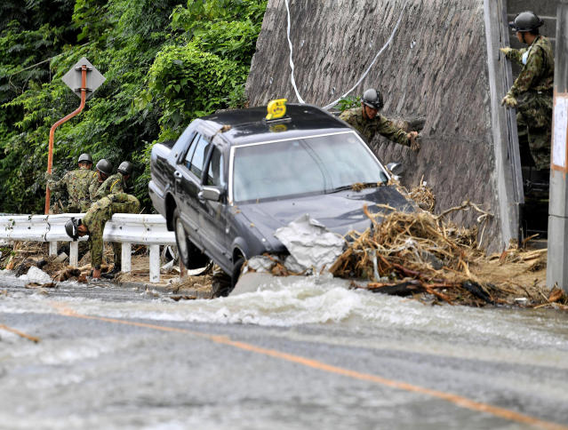 <p>Japan Ground Self-Defense Force members search missing people near a damaged taxi after flooding caused by heavy rains hit Hiroshima, southwestern Japan, Thursday, July 12, 2018. (Photo: Ryosuke Ozawa/Kyodo News via AP) </p>