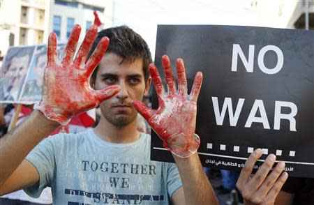 An activist shows his hands while wearing gloves covered in fake blood during a sit-in near the U.S. embassy in Awkar, north of Beirut, against potential U.S. strikes on Syria September 6, 2013. REUTERS/Mohamed Azakir