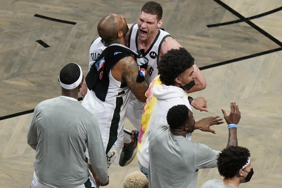 Milwaukee Bucks' Brook Lopez, right, celebrates with P.J. Tucker, left, and other teammates during overtime of Game 7 of a second-round NBA basketball playoff series Saturday, June 19, 2021, in New York. (AP Photo/Frank Franklin II)