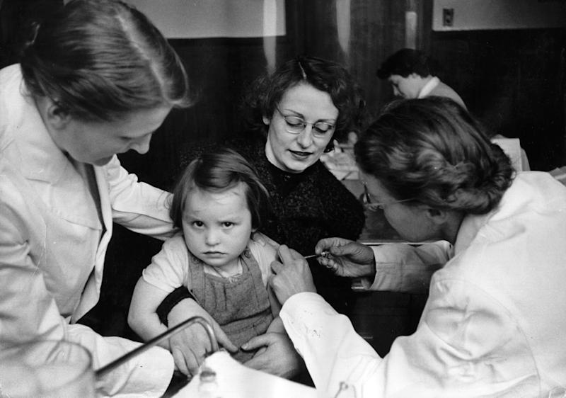 A rather reluctant-looking girl receives the polio vaccine in Britain in 1956. (Thurston Hopkins via Getty Images)