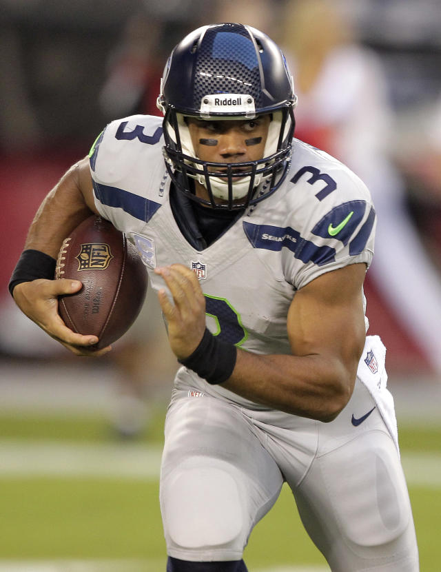Seattle Seahawks quarterback Russell Wilson runs against the Arizona Cardinals during the first half of an NFL football game, Thursday, Oct. 17, 2013, in Glendale, Ariz. (AP Photo/Rick Scuteri)