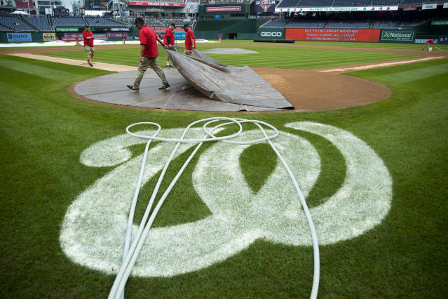 Members of the grounds crew remove a home plate tarp before a baseball game between the Washington Nationals and the New York Mets at Nationals Park, Sunday, Sept. 23, 2018, in Washington. (AP Photo/Andrew Harnik)