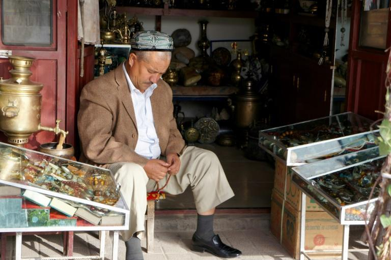 Rights groups say up to one million Uyghur Muslims, such as this man holding prayer beads in a shop in Kashgar, are detained in Chinese internment camps