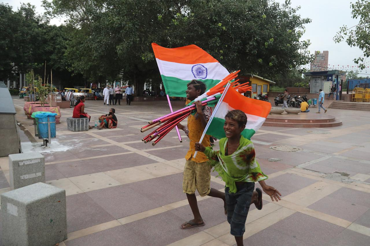 NEW DELHI, INDIA - 2020/08/14: Children sell Tricolour flags on the eve of Independence Day at Connaught Place.India 74th Independence day preparation Indian Prime Minister Narendra Modi will deliver his 7th Independence day speech from the rampart of Red fort on Saturday, an address that comes amid the coronavirus pandemic, a border standoff with China and his government's achievements. (Photo by Naveen Sharma/SOPA Images/LightRocket via Getty Images)