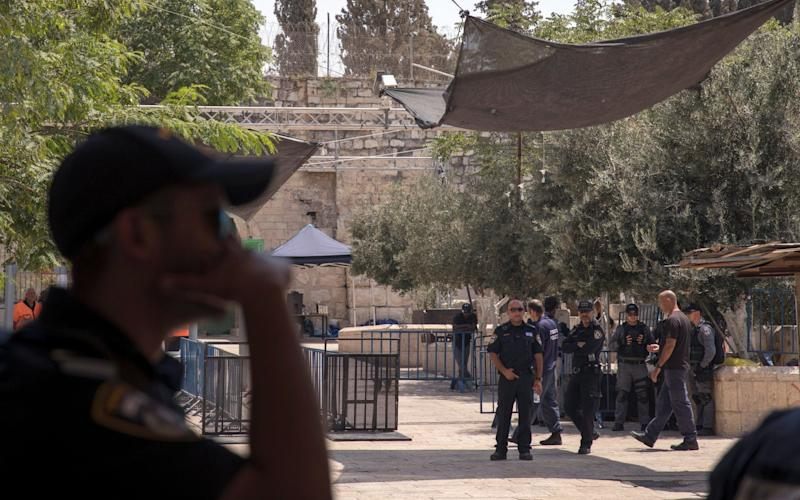 Israeli policeman guarding outside Lions' Gate, the main the entrance to the al-Aqsa compound next to the metal detectors, and a new cameras installed (top of the picture), as part of the new security measures - Credit: EPA