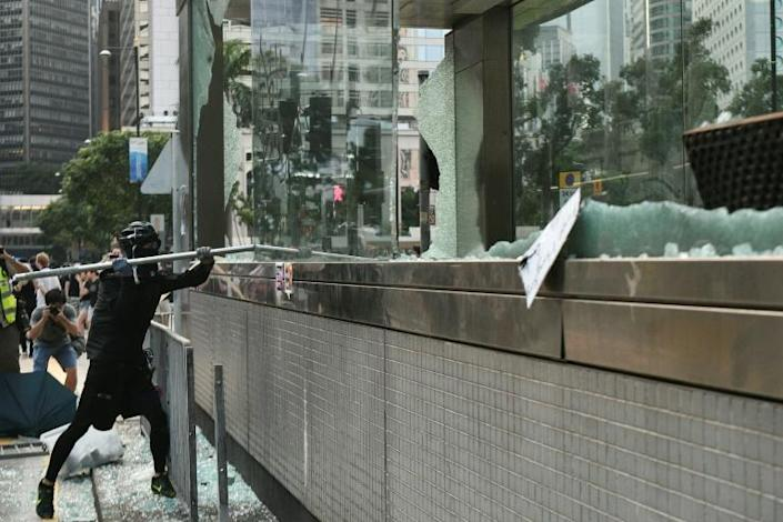 A hardcore Hong Kong protester uses a metal pole to smash glass outside an exit of the Central MTR underground metro station (AFP Photo/Anthony WALLACE)