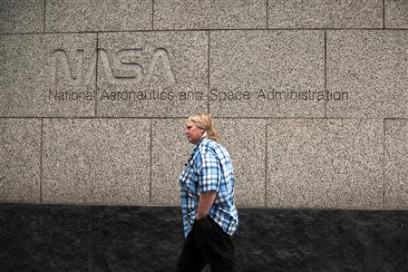 A woman walks past the NASA headquarters on Tuesday morning after the federal government was shutdown when the House and Senate failed to pass a budget in Washington October 1, 2013. REUTERS/James Lawler Duggan