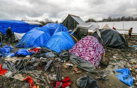 Migrants walk among tents in a muddy field at a camp of makeshift shelters called the Grande Synthe jungle, near Calais