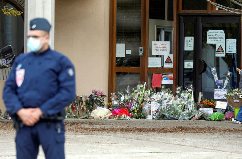 People bring flowers to the Bois d'Aulne college after the attack in the Paris suburb of Conflans St Honorine