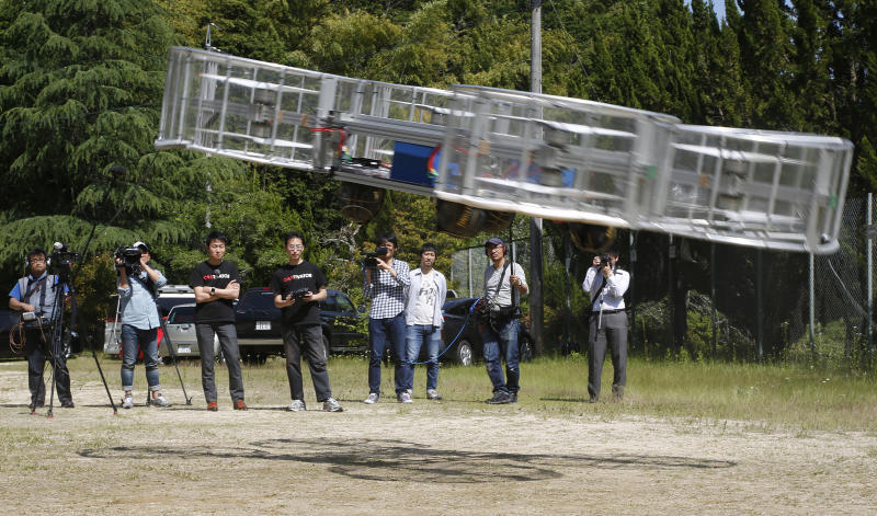 "FILE - In this Saturday, June 3, 2017, file photo, Tsubasa Nakamura, project leader of Cartivator, third from left, watches the flight of the test model of the flying car on a former school ground in Toyota, central Japan. The Japanese government has started a ""flying car"" project, bringing together more than a dozen companies, including All Nippon Airways, electronics company NEC, Toyota-backed startup Cartivator and Uber, the ride-hailing service. Toyota and its group companies have also invested 42.5 million yen ($375,000) in a Japanese startup, Cartivator, that is working on a flying car. (AP Photo/Koji Ueda, File)"