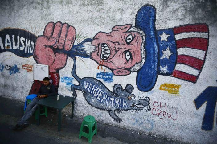 """A man sits next to graffti, which reads """"traitor"""", in Caracas March 9, 2015. The United States on Monday declared Venezuela a national security threat and ordered sanctions against seven officials from the oil-rich country in the worst bilateral diplomatic dispute since socialist President Nicolas Maduro took office in 2013. U.S. President Barack Obama issued and signed the executive order, which senior administration officials said did not target Venezuela's energy sector or broader economy. But the move stokes tensions between Washington and Caracas just as U.S. relations with Cuba, a longtime U.S. foe in Latin America and key ally to Venezuela, are set to be normalized. REUTERS/Jorge Silva (VENEZUELA - Tags: POLITICS)"""