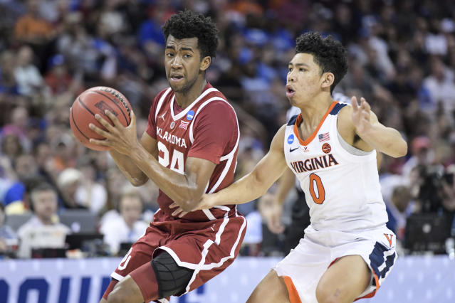 Oklahoma guard Jamal Bieniemy (24) drives to the hoop against Virginia guard Kihei Clark (0) during the first half of a second-round game in the NCAA men's college basketball tournament Sunday, March 24, 2019, in Columbia, S.C. (AP Photo/Sean Rayford)