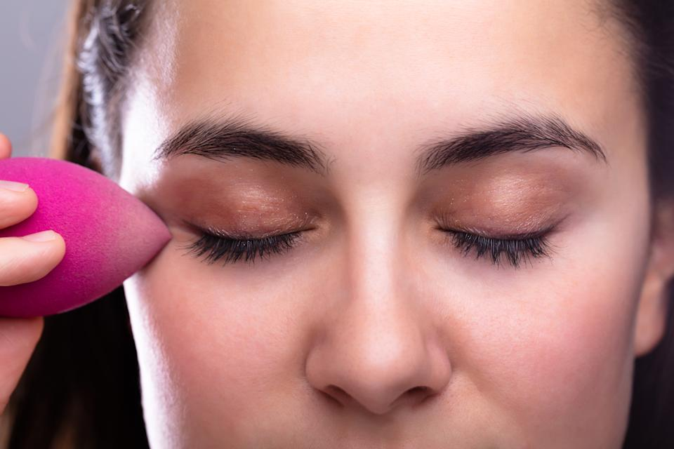 Pretty Woman Using Pink Sponge Blender Make Up Tool On Face