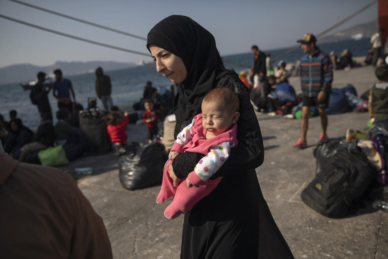 Sixteen-year-old Montaha from Aleppo, Syria, walks with her 2-month-old daughter, Batour, after their arrival at the port of Elefsina, near Athens, Greece, October 2019. (Photo: Petros Giannakouris/AP)