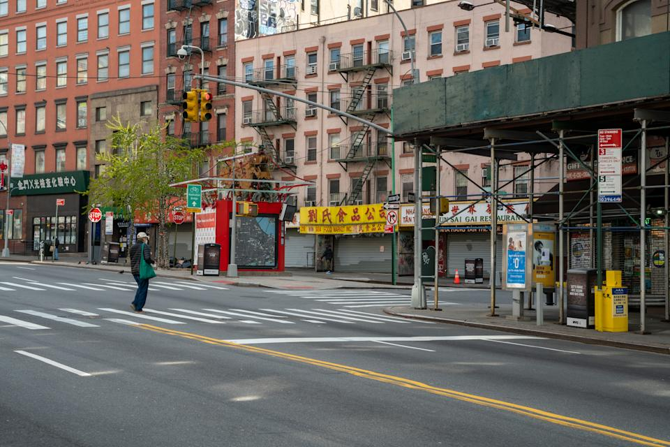 NEW YORK, NY - APRIL 16: A person walks in a desolate Chinatown shopping area on April 16, 2020, in New York City. New York State Governor Andrew Cuomo announced during his daily COVID-19 briefing that the