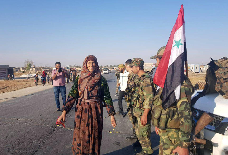 In this photo released by the Syrian official news agency SANA, residents welcome Syrian soldiers shortly after they entered the northern town of Tal Tamr on Monday, Oct 14, 2019. The move toward Tal Tamr came a day after Syria's Kurds said Syrian government forces agreed to help them fend off Turkey's invasion — a major shift in alliances that came after President Donald Trump ordered all U.S. troops withdrawn from the northern border area amid the rapidly deepening chaos. (SANA via AP)