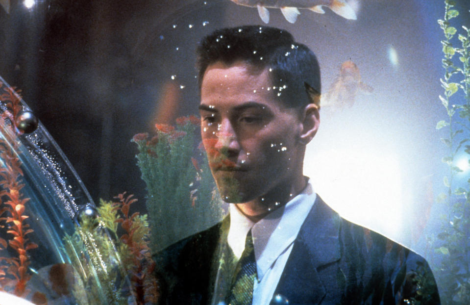 Keanu Reeves looks into an aquarium in a scene from the film 'Johnny Mnemonic', 1995. (Photo by TriStar/Getty Images)
