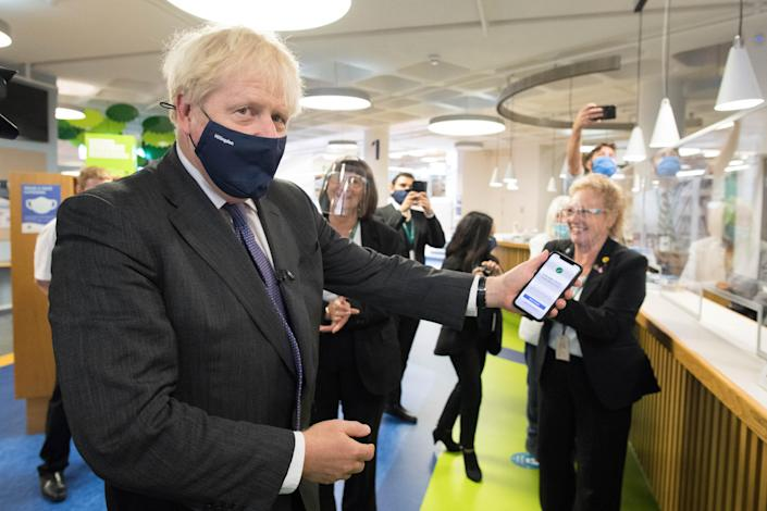 Boris Johnson scans his NHS Coronavirus App at Uxbridge Library earlier this week. (PA)