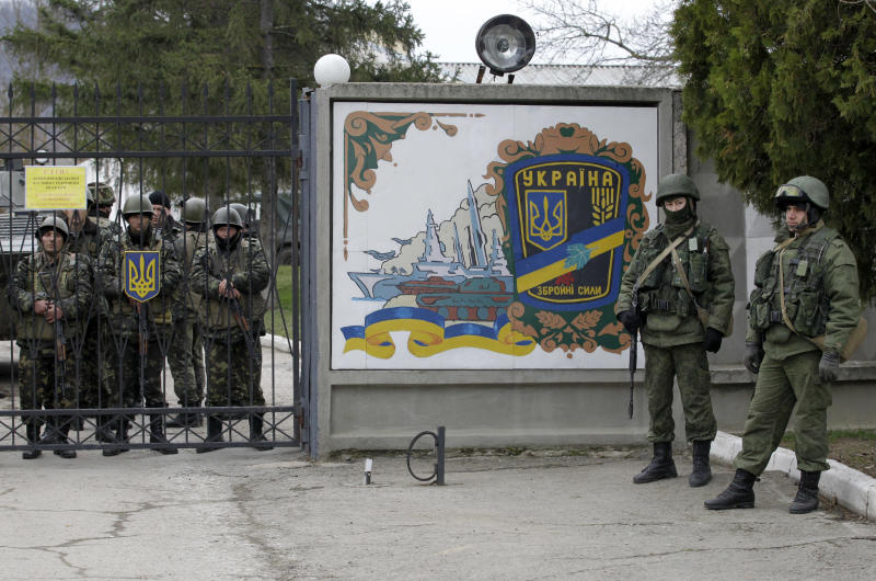 Ukrainian soldiers, left and unidentified gunmen, right, guard the gate of an infantry base in Privolnoye, Ukraine, Sunday, March 2, 2014. Hundreds of unidentified gunmen arrived outside Ukraine's infantry base in Privolnoye in its Crimea region. The convoy includes at least 13 troop vehicles each containing 30 soldiers and four armored vehicles with mounted machine guns. The vehicles — which have Russian license plates — have surrounded the base and are blocking Ukrainian soldiers from entering or leaving it. (AP Photo/Darko Vojinovic)