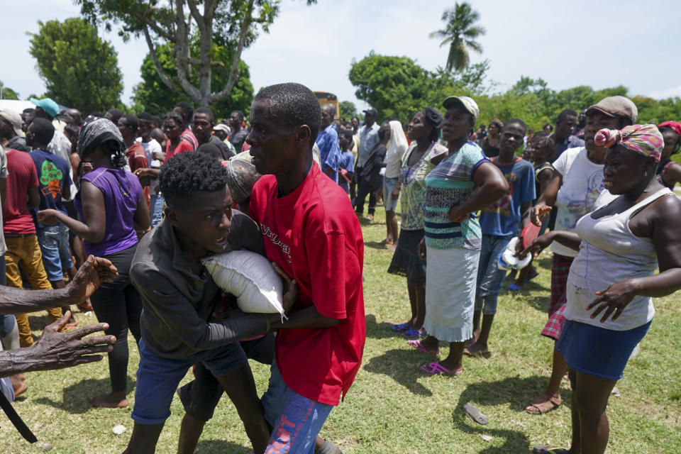 Men scuffle over a sack of donated food taken from a truck loaded with relief supplies, in Vye Terre, Haiti, Friday, Aug. 20, 2021. Private aid and shipments from the U.S. government and others were arriving in the country's southwestern peninsula that was struck by a 7.2 magnitude quake on Aug. 14. (AP Photo/Fernando Llano)