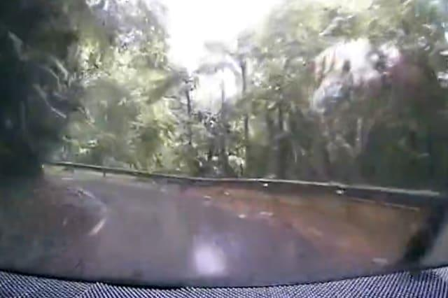 Landslide crashes onto road just yards from an oncoming car during storm in Malaysia