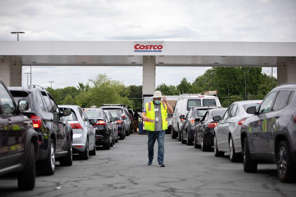 Attendants direct cars as they line up to fill their gas tanks at a COSTCO on Tyvola Road in Charlotte, North Carolina on May 11, 2021. - Fears the shutdown of a major fuel pipeline would cause a gasoline shortage led to some panic buying and prompted US regulators on May 11, 2021 to temporarily suspend clean fuel requirements in three eastern states and the nation's capital. A ransomware attack Friday on Colonial Pipeline forced the company to shut down its entire network, though industry experts say any shortages will be temporary. (Photo by Logan Cyrus / AFP) (Photo by LOGAN CYRUS/AFP via Getty Images)