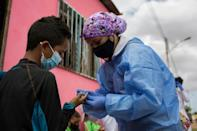 A volunteer with Doctors Without Borders (MSF) takes a blood sample to be tested for malaria in the town of Barcelona, Anzoategui State, Venezuela