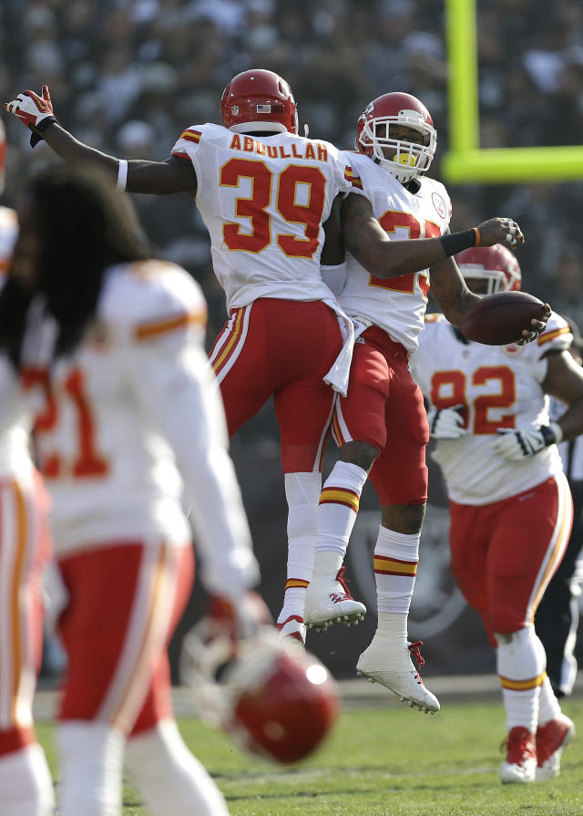 Kansas City Chiefs strong safety Eric Berry, top right, celebrates with defensive back Husain Abdullah (39) after returning an interception by Oakland Raiders quarterback Matt McGloin for a 47-yard touchdown during the first quarter of an NFL football game in Oakland, Calif., Sunday, Dec. 15, 2013. (AP Photo/Marcio Jose Sanchez)