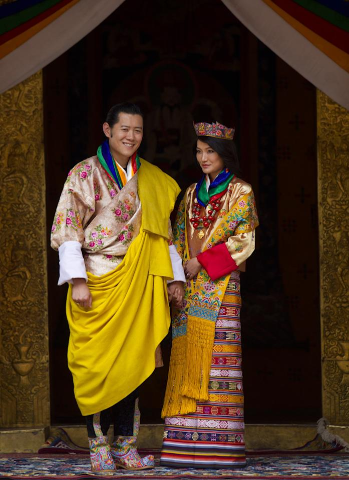 PUNAKHA, BHUTAN - OCTOBER 13: His majesty King Jigme Khesar Namgyel Wangchuck, 31, holds his Raven crown as he and the Queen Jetsun Pema, 21, walk out after their marriage ceremony is completed on October 13, 2011 in Punakha, Bhutan. The Dzong is the same venue that hosted the King's historic coronation ceremony in 2008. The Oxford-educated king is popular in the country and the ceremony will be followed by celebration in the capital and countryside.  (Photo by Paula Bronstein/Getty Images)