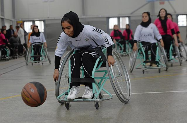 An Afghan member of the Mazar-i-Sharif wheelchair basketball team plays against the team from Kabul during the final of the country's third annual competition in Kabul on October 29, 2014 (AFP Photo/Shah Marai)