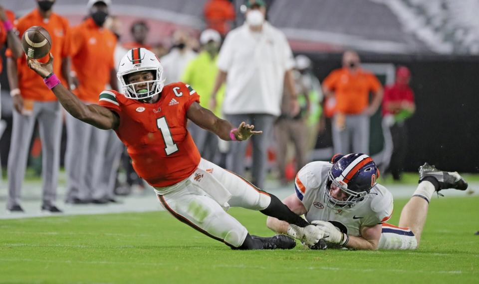 Miami quarterback D'Eriq King (1) is tackled by Virginia's Zane Zandier (1) in the first half of an NCAA college football game in Miami Gardens, Fla., Saturday, Oct. 24, 2020. (Al Diaz/Miami Herald via AP)