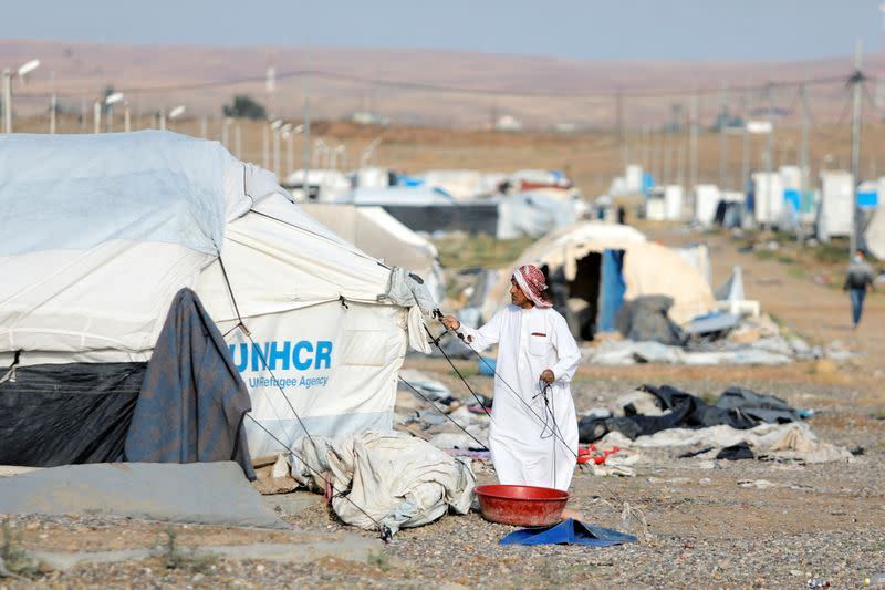 A displaced Iraqi man dismantles his tent as he prepares to be evacuated, at Hammam Al-Alil camp, south of Mosul
