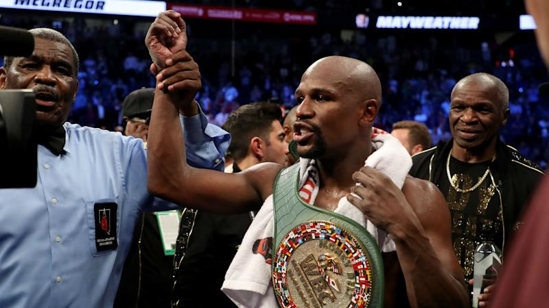 Boxer Floyd Mayweather flaunts $100million cheque he earned after beating Conor McGregor