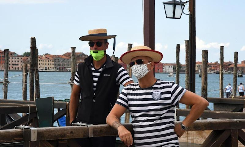 Gondoliers wearing protective face masks wait for tourists.