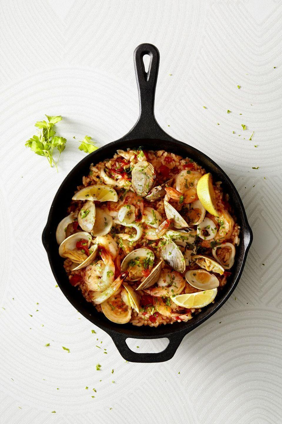 """<p>With clams, shrimp and squid, this savory seafood is much easier to make than it looks.</p><p><em><a href=""""https://www.goodhousekeeping.com/food-recipes/a42820/easiest-ever-paella-recipe/"""" rel=""""nofollow noopener"""" target=""""_blank"""" data-ylk=""""slk:Get the recipe for Easiest-Ever Paella »"""" class=""""link rapid-noclick-resp"""">Get the recipe for Easiest-Ever Paella »</a></em></p>"""